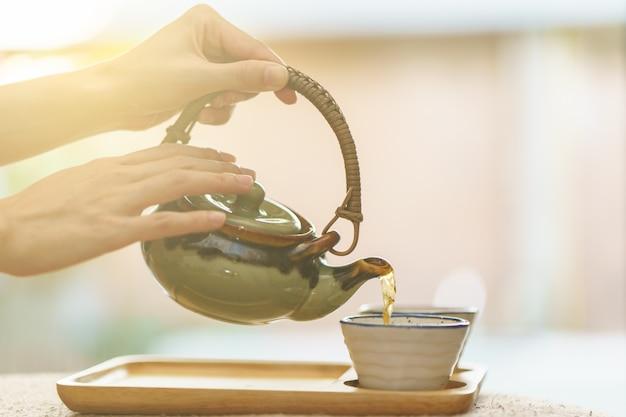 Chá quente da panela em uma xícara de chá de vidro.