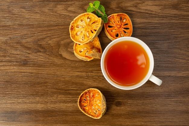 Chá quente de bael de frutas secas em uma xícara tailandesa de ervas