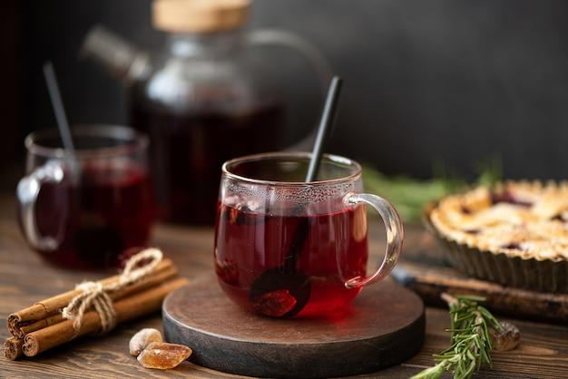 Chá quente de hibisco com canela e açúcar em uma mesa de madeira