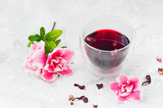 Chá quente de hibisco em uma caneca com flores rosa