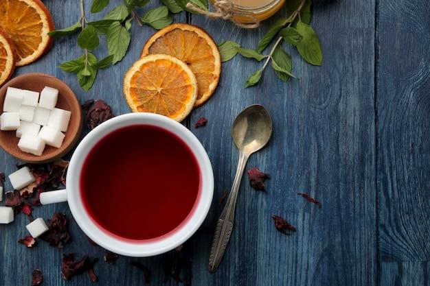 Chá quente de karkade vermelho com mel e hortelã em uma mesa de madeira azul.