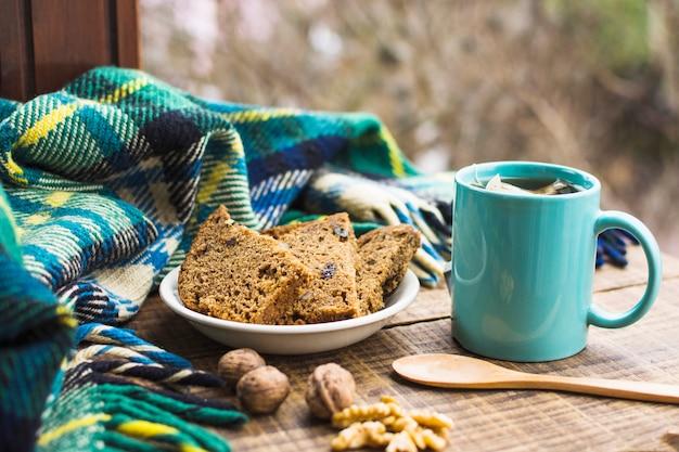 Chá quente e lanche na mesa perto de cobertor