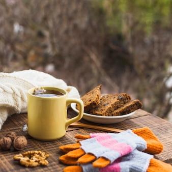 Chá quente e sobremesa perto de camisola e luvas