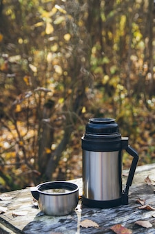 Chá quente e uma garrafa térmica em cima da mesa no outono
