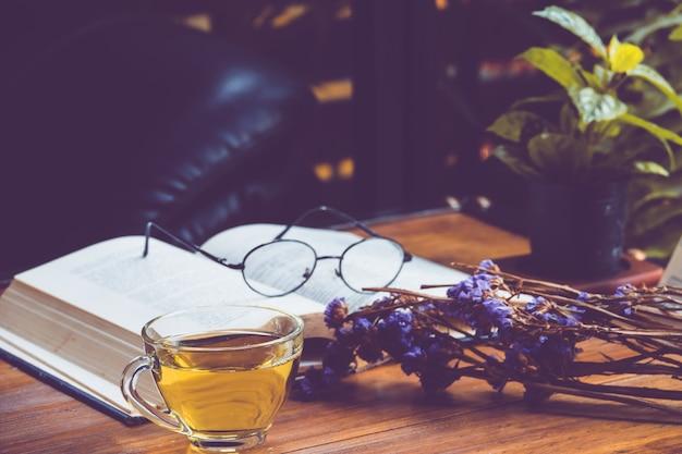 Chá quente em um copo com um livro antigo e flor na mesa