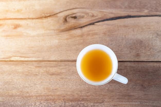 Chá quente em um copo no fundo da mesa de madeira com espaço de cópia