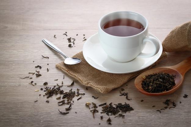 Chá quente em vidro branco colocado sobre uma mesa de madeira.