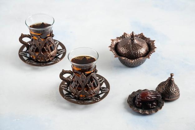 Chá quente fresco e tâmara seca na superfície branca