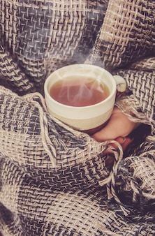 Chá quente na panela perto da janela. foco seletivo.