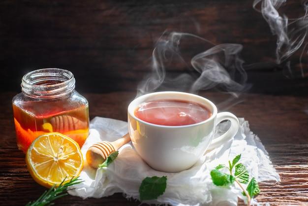 Chá quente no bule de vidro e copo com vapor no fundo de madeira
