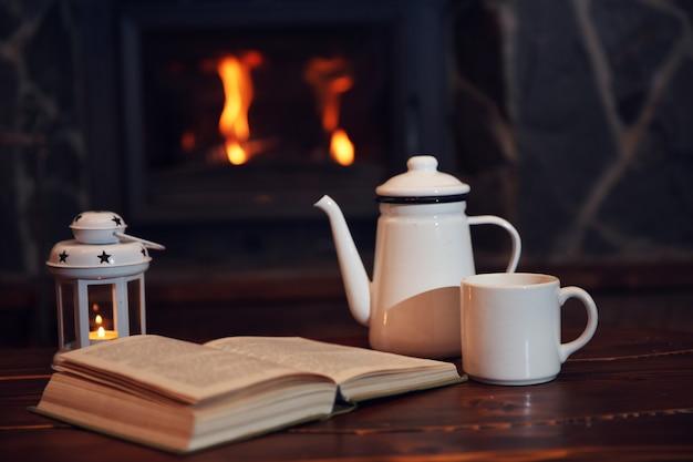 Chá quente ou café na caneca, livro e velas na mesa de madeira vintage. lareira como pano de fundo