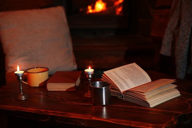 Chá quente ou café na caneca, livro e velas na mesa de madeira vintage.
