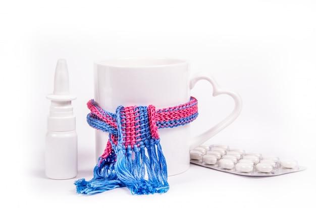 Chá quente, spray nasal e comprimidos em fundo branco