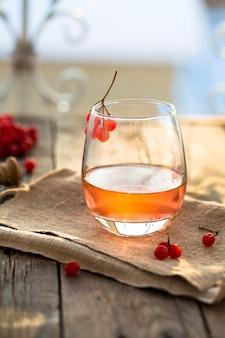 Chá quente viburnum em um copo com uma mesa de madeira cinza, ao lado de bagas frescas viburnum. chá saudável viburnum