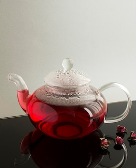 Chá rosa com rosas no bule de vidro na mesa preta. fechar-se.