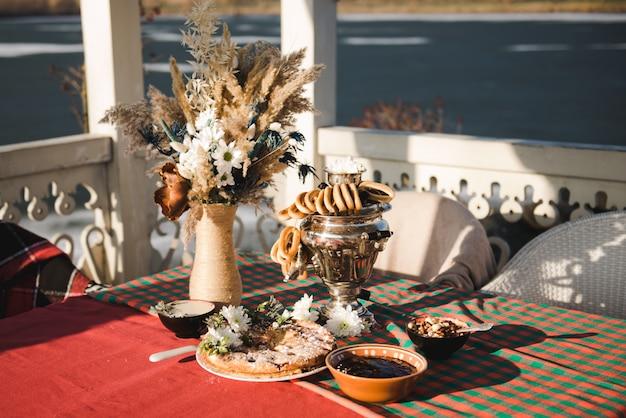 Chá russo de samovar. festa de chá de inverno na natureza. torta com frutas. samovar com composição de bagels