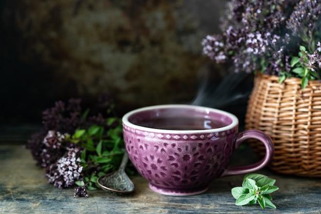 Chá saudável de flores de orégano em uma bela caneca em um fundo de madeira. copie o espaço