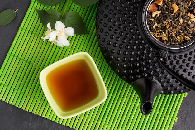 Chá saudável na tigela de cerâmica com folhas secas no tapete de lugar verde