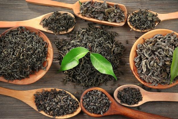 Chá seco com folhas verdes em colheres de madeira na superfície da mesa