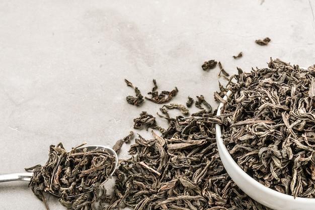 Chá seco em um copo de cerâmica branca com uma colher em um cinza texturizado