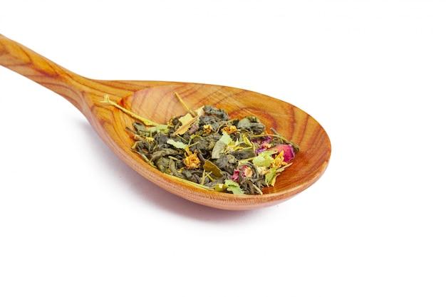 Chá seco em uma colher de pau, isolado no branco