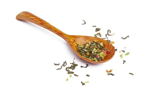 Chá seco em uma colher de pau, isolado