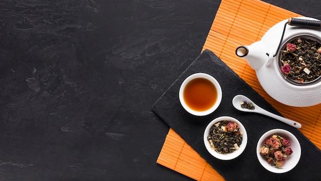 Chá seco erva e flor de orquídea rosa e pano de fundo texturizado preto
