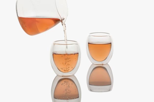 Chá servindo em uma xícara de chá de vidro de parede dupla, isolada em branco