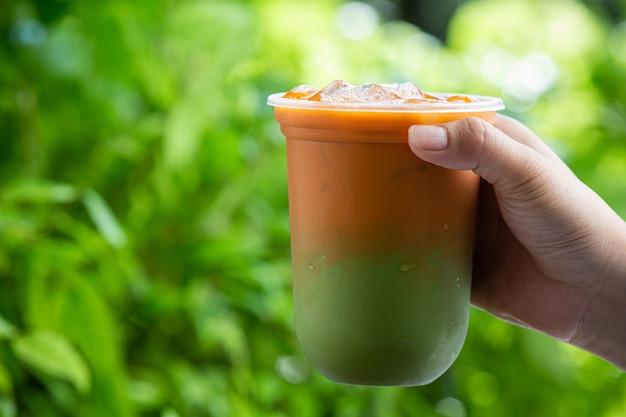 Chá tailandês gelado misturado com chá verde em superfície de madeira