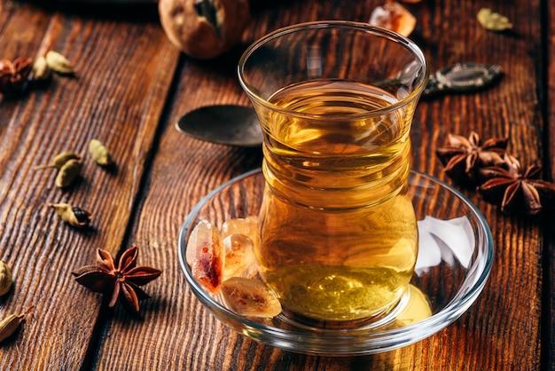 Chá temperado com anis estrelado, cardamomo e lima seca em copo armudu sobre superfície de madeira