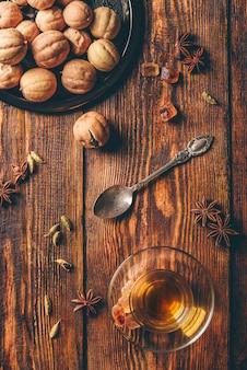 Chá temperado com anis estrelado, cardamomo e lima seca em vidro árabe sobre superfície de madeira