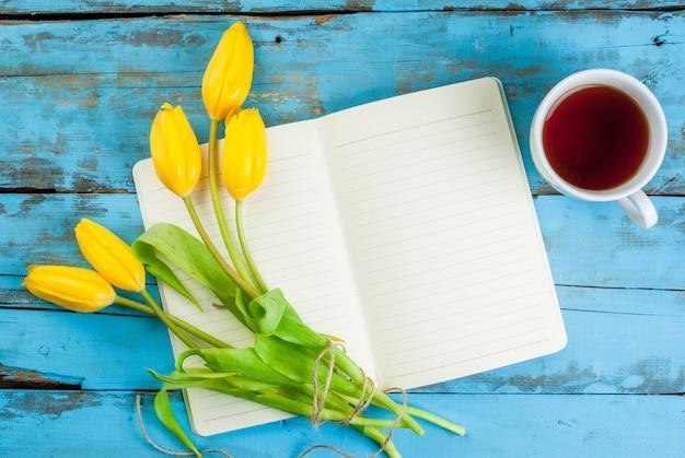 Chá, tulipas e caderno na mesa azul