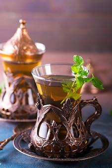 Chá turco tradicional com folhas de hortelã em um copo tradicional em concreto