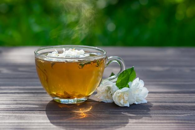 Chá verde com flores de jasmim na mesa de madeira