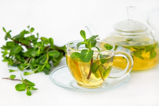 Chá verde com hortelã em uma xícara e um bule de vidro transparente sobre uma mesa branca.