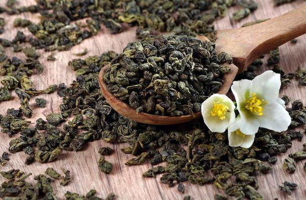 Chá verde com jasmim. folhas de chá verde em uma colher de pau e flores de jasmim.