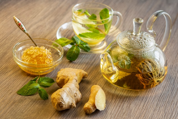 Chá verde com limão e hortelã em uma tigela de vidro transparente, gengibre e mel em favos de mel em uma mesa de madeira