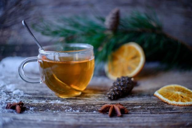 Chá verde com uma xícara de vidro em uma mesa de madeira com galhos de pinheiro, laranjas secas, pinhas, estrelas de anis e neve