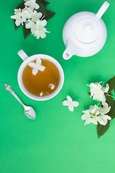 Chá verde de jasmim na xícara com bule e flores