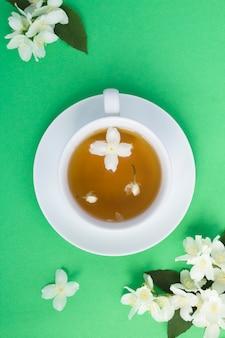 Chá verde de jasmim na xícara com flores