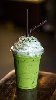Chá verde do matcha gelado no copo afastado isolado na tabela de madeira