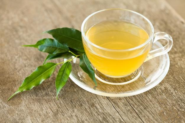 Chá verde em copo de vidro na mesa de madeira