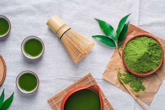 Chá verde em pó com folha em prato de cerâmica em cima da mesa, batedor de arame japonês feito de bambu para a cerimônia do chá matcha