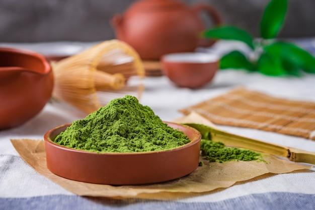 Chá verde em pó com folha em prato de cerâmica em cima da mesa, batedor de arame japonês feito de bambu para cerimônia de chá macha