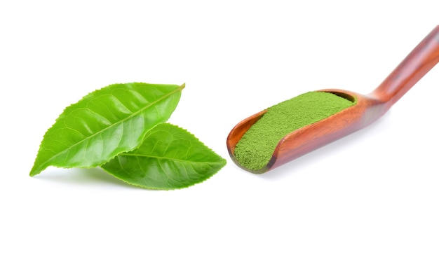 Chá verde em pó com folhas de chá verde em fundo branco.