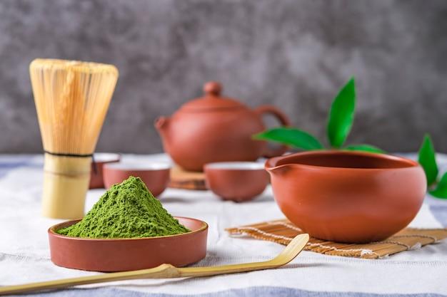 Chá verde em pó com folhas em prato de cerâmico em cima da mesa, batedor de arame japonês feito de bambu