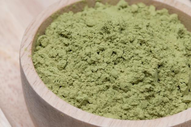 Chá verde em pó no copo de madeira.