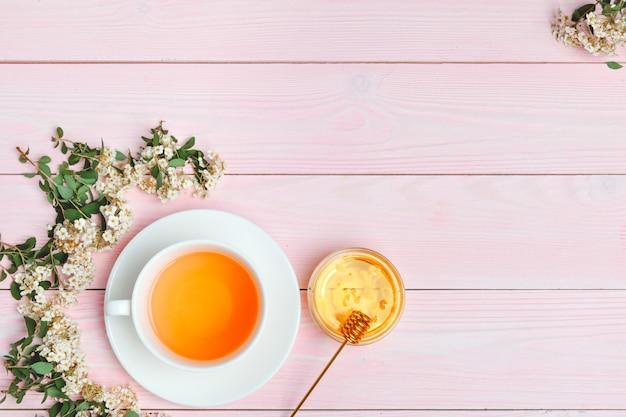 Chá verde em uma xícara de cerâmica com galhos de galhos de árvores florescendo