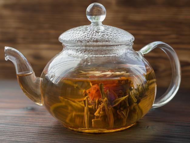 Chá verde exótico com flores em bule de vidro