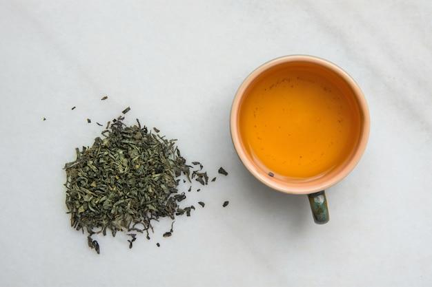Chá verde fermentado em copo de cerâmica. folhas fracas dispersadas no fundo de pedra de mármore branco.